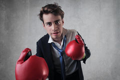 Bravery. Young businessman with boxing gloves stock photos
