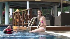 Bravez l'enfant ayant l'amusement sautant dans la piscine banque de vidéos