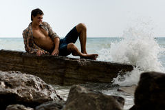 Brawny lad on stone at sea Royalty Free Stock Photos