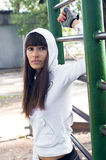 Brawny sport girl. Pretty brawny sport brunette woman with long brunette hair outdoors wearing white hoodie with a hood on and sport gauntlets, standing near Royalty Free Stock Photography