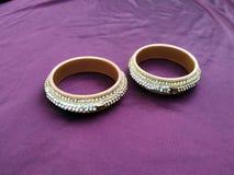Brazaletes indios Pulsera con los diamantes en el fondo violeta imágenes de archivo libres de regalías