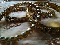 Brazaletes puros del oro en fondo de seda marrón imagenes de archivo