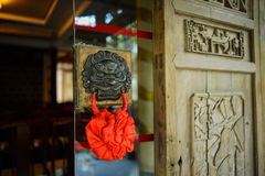 Brazen door knocker,China. A brazen door knocker on the glass door leaf,Chengdu,China Stock Image