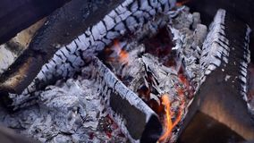 Brazier from barrel of firewood. Shot in slow motion. Close-up of bbq fireplace outdoors. Burning wood and coals stock video footage