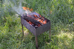 The brazier with burning firewood costs on a grass Stock Photo