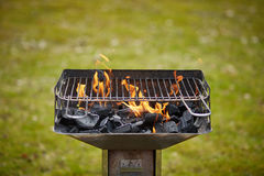 A brazier with charcoal and flame in it. On the grass Royalty Free Stock Photos