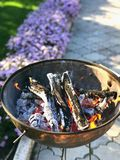 Brazier with a fire, logs and charcoal in the open air. royalty free stock images