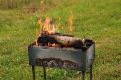 In a brazier firewood burns... Firewood in a brazier burns. Pieces of coal for a picnic in the fresh air are prepared royalty free stock photos
