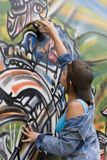 Brazil. Model Release 373  Beautiful Brazilian girl spray painting a mural on the side of a building Stock Photography