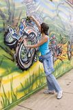 Brazil. Beautiful Brazilian girl spray painting a mural on the side of a building Stock Photos