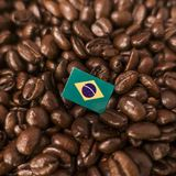 A Brazil, Brasil flag placed over roasted coffee beans stock photography