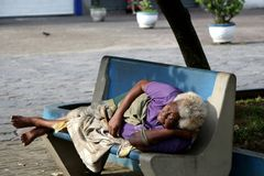 Brazil - elderly woman waking up after sleeping on the bank of the square. One Sunday morning the blatant of a miserable sexagenarian homeless after sleeping on stock photography