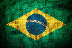 Brazil flag on coffee sack texture. Concept of raw coffee beans import and export royalty free stock photography