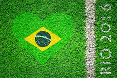 Brazil flag on grass with Rio summer Olympics background. Artificial soccer grass field detail with white goal line, textured Brazil flag and Rio 2016 words stock photography