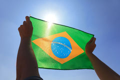 Brazil flag. In hand with sky and sun stock photography