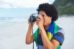 Brazil flag man beach. Man with Brasil flag taking photos at the beach Stock Photo