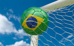 Brazil flag and soccer ball in goal net Stock Images