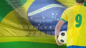 Brazil Flag Video. Brazil Flag blowing in the wind at stadium with football player holding football stock video footage