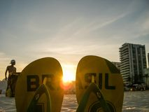 Brazil - Flip flops on the beach. Flip flops with sign `Brazil` placed in the sand on the Copacabana Beach in Brazil. between the shoes the sun starts setting royalty free stock photo