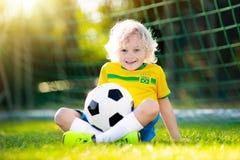Brazil football fan kids. Children play soccer. Kids play football on outdoor field. Brazil team fans. Children score a goal at soccer game. Little boy in royalty free stock photo