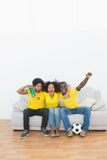 Brazil football fans sitting on couch cheering together Stock Photos