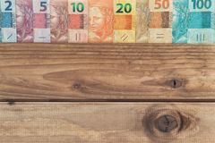 Brazilian money all denominations on the wooden background  with place for a text. Brazil money all denominations on the wooden background  with place for a Royalty Free Stock Images