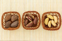 Brazil Nuts in baskets over bamboo mat. Royalty Free Stock Photos