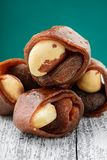 Dried fruits on a turquoise background. Brazil nuts, dried apricots and black fruit pastille on a turquoise background Royalty Free Stock Photography