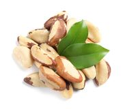 Brazil nuts with green leaves on white background. Brazil nuts with green leaves isolated on white background, top view stock images