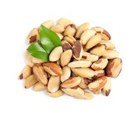 Brazil nuts with green leaves on white background. Top view royalty free stock photography