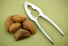 Brazil nuts with nut cracker on textured background Royalty Free Stock Image