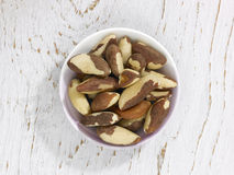 Brazil Nuts. A selection of Brazil nuts in a bowl on a white wooden surface Royalty Free Stock Photo