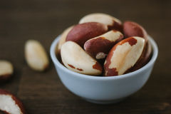 Brazil nuts on white ceramic bowl over the wooden table Stock Image