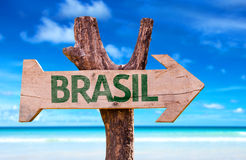Brazil (in Portuguese) wooden sign with a beach on background. Brazil wooden sign with a beach on background Royalty Free Stock Photos