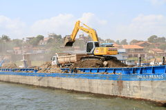 Excavator Emptying a Barge Stock Photography
