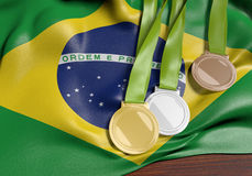 Brazil and 2016 summer games sports competition, 3D rendering. 3D render of gold, silver, and bronze medals lying over the country flag of Brazil for the 2016 Royalty Free Stock Images
