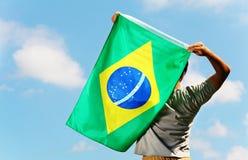 Brazil supporter holding flag. Brazil supporter holding a flag stock photos