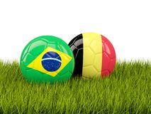 Brazil vs Belgium. Soccer concept. Footballs with flags on green Royalty Free Stock Photography