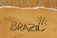 Brazil word on sand beach. With waves background royalty free stock photography
