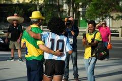 Braziliaanse ventilator naast een mens gekleed als Maradona Stock Fotografie