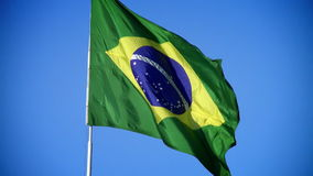 Braziliaanse vlag die bij wind met een blauwe hemel golven stock video