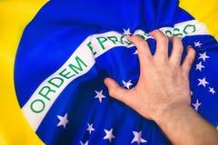 Braziliaanse vlag met een hand royalty-vrije stock afbeeldingen