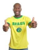 Braziliaanse voetbalventilator die beide duimen tonen Royalty-vrije Stock Fotografie