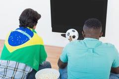 Braziliaanse voetbalventilators die op TV letten Stock Foto