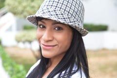 Braziliaanse vrouw die met hoed bij camera glimlachen stock fotografie