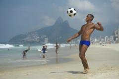 Brazilian Altinho Athletic Young Brazilian Man Beach Football. Brazilian altinho player young athletic carioca man juggling football soccer ball on the beach in Stock Photos