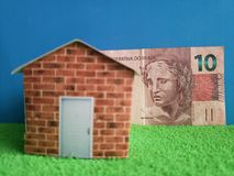 Brazilian banknote, figure of a house on green surface and blue background. Backdrop for mortgage and housing value ads, loan for home construction and stock images