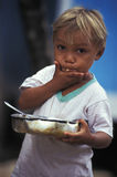 Brazilian blond child eating from saucepan. Brazilian child eating farofa from a saucepan in the Amazon. Farofa is a savory side dish made with manioc flour and Royalty Free Stock Image
