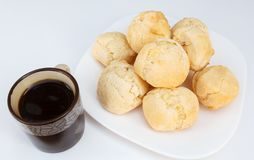 Brazilian breakfast, cheese bread pao de queijo served on dish on white table with coffee stock photography
