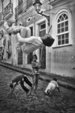 Brazilian capoeira, Pelourinho, Salvador, Bahia, Brazil. Brazilian capoeirista man with all white clothes doing a backflip. There are two kids in the background royalty free stock images